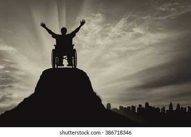 Concept of disability and disease. Silhouette happy disabled person in a wheelchair on the background of the urban landscape