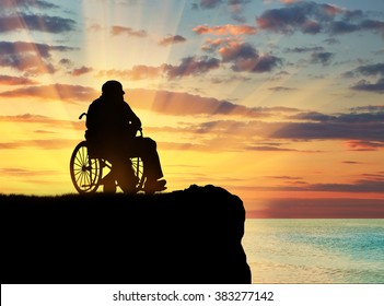Concept of disability and old age. Silhouette of disabled person in a wheelchair on a hill against a sunset sea