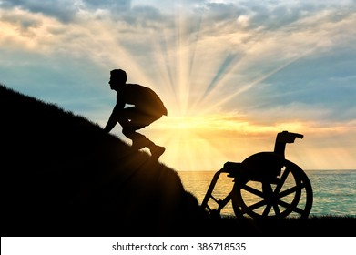 Concept of disability and self-motivated. Silhouette of disabled person to climb the hill on a background of sea sunset