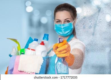 Das Konzept der Desinfektion und Reinigung im Haus. Die Reinigungskraft sprüht aus dem Spray auf Glas.