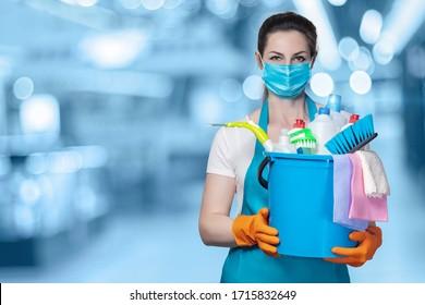 Das Konzept der Desinfektion und Reinigung. Die Dame in der Maske mit einem Eimer Reinigungsprodukte auf unscharfem Hintergrund.