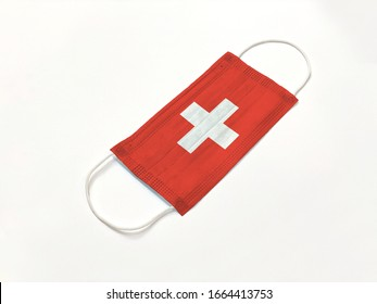 Concept. Disposable medical surgical face mask with Switzerland country flag superimposed on it, on white background. Protection against Covid-19 coronavirus outbreak.