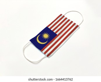 Concept. Disposable medical surgical face mask with Malaysia country flag superimposed on it, on white background. Protection against Covid-19 coronavirus outbreak.