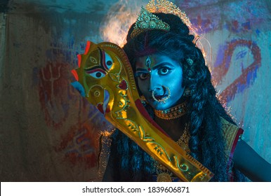 Concept Diwali  &  'KALI PUJA' Festival shoot with black haired Indian brunette Bengali woman  wearing jewellery  like goddess  at a smoky place,