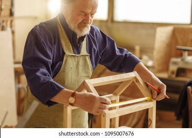 concept of diy. old man is making a sketch of birds house from wood