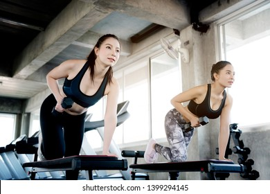 Concept of doing business, opening gym Asian women are workout using dumbbells to reduce arms. Increase strength of muscles. Regular exercise will result in a balanced shape and good mental health.