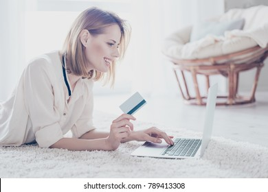 Concept of doing shopping without leaving your house. Close up portrait of happy cheerful joyful cute beautiful woman, who is using the internet and credit card for buying goods online