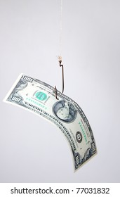 The concept. Dollars as a bait hang on a hook against the gray background