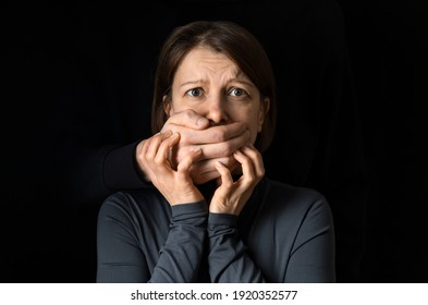 The concept of domestic violence against a woman. The male hand closes the female mouth.