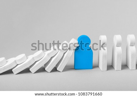 Concept of domino effect in business. Fall of the crumbling business is saved by special employee leader. The line of dominoes from the white figures of the man is falling, one blue man stops the fall