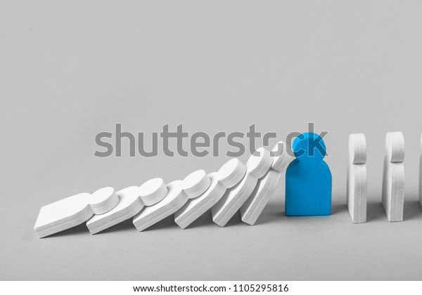 Concept of domino effect in business. The fall of the crumbling business is saved by special employee leader. The line of dominoes from the white figures of the man is falling, one man stops the fall.