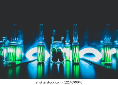concept of doping in sport. Bright ampoules with luminous green contents: Diuretics, Peptide hormones, Anabolic steroids, Painkillers, Stimulants. artistic dark filter. low key photo.