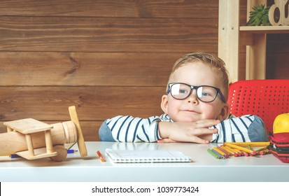 Concept of dreams and travels. Happy smiling child in glasses at school. want to travel. Apple, books, toy airplane on desk over wooden table. Set of back to school.