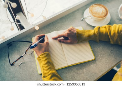 Concept of drinks and youth lifestyle, woman hands and cup of coffee. Young woman writing to do list of goals writing in diary in coffee shop. Female student taking notes in personal organizer.