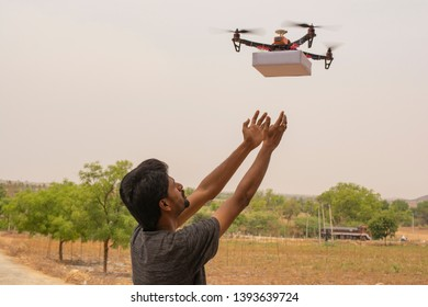 Concept of Drone delivery,Young man receiving the product from flying drone