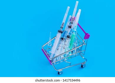 Concept of drug treatment. Take the treatment ordered by the doctor. The consumer's basket on a blue background with many drugs. Ampoules with vaccine and syringes for injections.