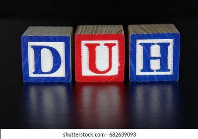 The concept DUH spelled out in toy alphabet block on a black background. Used to comment on an action perceived as foolish or stupid, or a statement perceived as obvious.