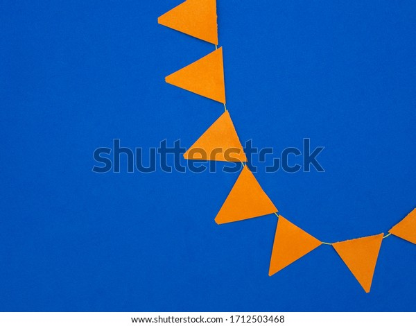 Concept for the Dutch holiday called Koningsdag (Kings day) or other Dutch orange festivities. Orange flags on a blue background. Room for text.