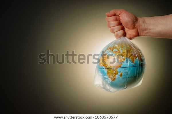 The concept of Earth Day. The man's hand holds the earth in a plastic bag. The globe closes the sun forming a solar eclipse. In the blank for social advertising there is a place for the inscription.