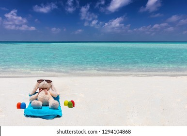 Concept of a easter bunny relaxing on a tropical beach with colourful easter eggs