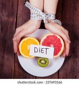 The concept of eating disorders: bulimia, anorexia, diet fads. Women's hands tied centimeter. Girl's hands with a plate and fruit. Fruit diet. Low-fat diet.