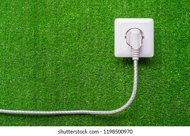 concept of ecological reception of an electricity. Electric socket and plug with a cord on a background of green grass
