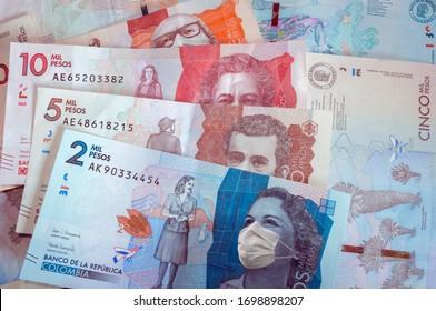 Concepto de crisis económica en Colombia debido a la pandemia causada por el coronavirus covid-19 representado en billetes con máscaras faciales