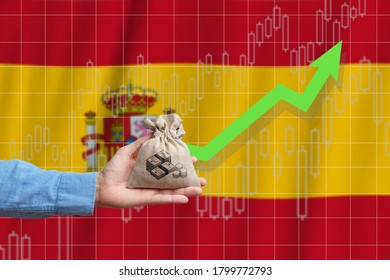 The concept of economic growth in Kingdom of Spain. Hand holds a bag with money and an upward arrow.