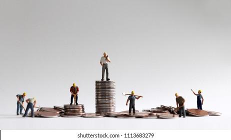 A concept of economic inequality. Pileofcoinsandminiaturepeople.