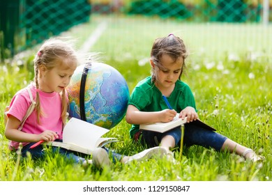 Concept - education. Back to school. Two cheerful Caucasian girls schoolgirls with a globe, happy to be returning home after class in class