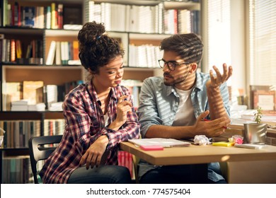 Concept of education, library, students, love and teamwork. innovative productive young studying couple sitting in the library, learning and consulting together from notes.