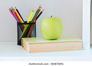 Concept of education. A yellow apple sitting on top of a book and pencils in holder on background