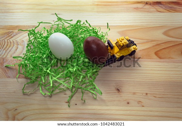 concept of egg hunt on Easter with toy loader gathering eggs