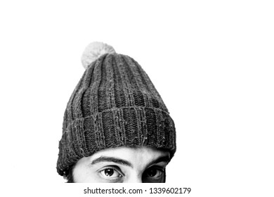 Concept of the end or the beginning of the winter. Young man with a winter hat staring at the camera at the bottom of the image. Subject in black and white, with a white background. Isolated