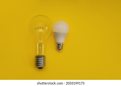 the concept of energy efficiency. a large incandescent bulb next to a small LED lamp. on a yellow background. copy space