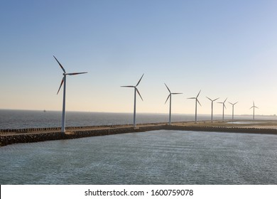 Concept of energy transition, alternative energies or environmental protection: wind turbines on the coast with sea in the foreground and in the background, lots of copy space
