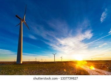 Concept of engineering and renewable energies. Ecology and environment.Eolic park and wind mills in sunset landscape and fields