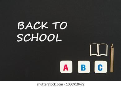 concept english school, text back to school, abc letters, chipboard miniature book, pen on blackboard