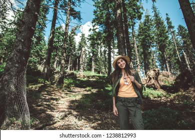Concept of enjoying journey and adventure. Full length portrait of happy young lady posing on camers standing on forest path. Copy space on left
