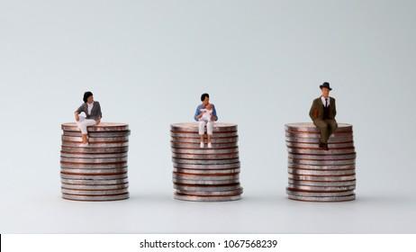 The concept of equal pay. Miniature women holding baby sitting on a pile of coins and two miniature people sitting on a pile of coins.