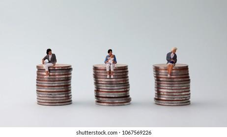 The concept of equal pay. Miniaturewomanholdingbabysittingonapileofcoinsandtwominiaturewomensittingonapileofcoins.