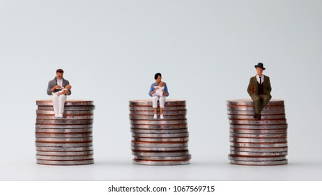 The concept of equal pay. A miniature man and a miniature woman holding babies.
