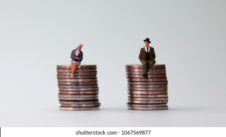 The concept of equal pay. A miniature man and a miniature woman sitting on a pile of coins of equal height.