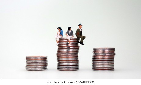 The concept of equal pay. A pile of coins and miniature people.