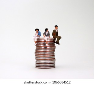 The concept of equal work and equal pay. A pile of coins and miniature people.