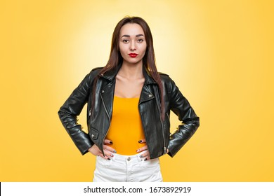 The concept of equality and feminism. An isolated shot of Caucasian woman in a leather jacket poses confidently on a yellow background. Copy