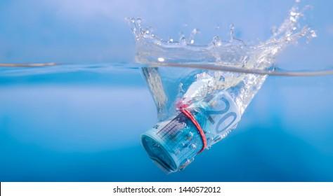 Concept: European debt crisis.  Euro banknote sinking in water.