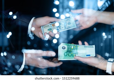 The concept of exchange of dollars for euros. The businessmans transfer dollars and euros on the blurred background.