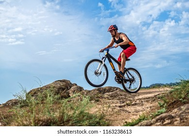 Concept of extreme cycling, a biker on a mountain bike on the blue sky background, free space. Cyclist in a helmet and with a backpack is riding down the rocks, mtb.