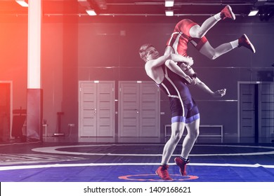 The concept of fair wrestling. Two greco-roman  wrestlers in red and blue uniform wrestling   on a wrestling carpet in the gym. The concept of fair wrestling